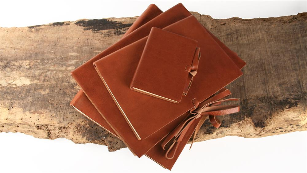 vegetable tanned rustico leather journals stacked on a rustic wooden surface